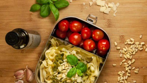 Lunchbox mit Trennwand, Pesto und Tomaten.