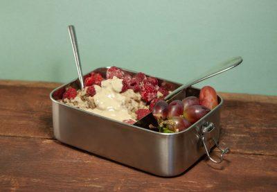 Auslaufsichere Lunchbox aus Edelstahl befüllt mit Porridge und Weintrauben