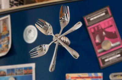 Drei Göffel hängen mit einem Magneten befestigt am Kühlschrank