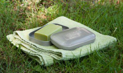 Nachhaltige Seifendose liegt mit einem Seifenstück und einem Handtuch auf dem Gras