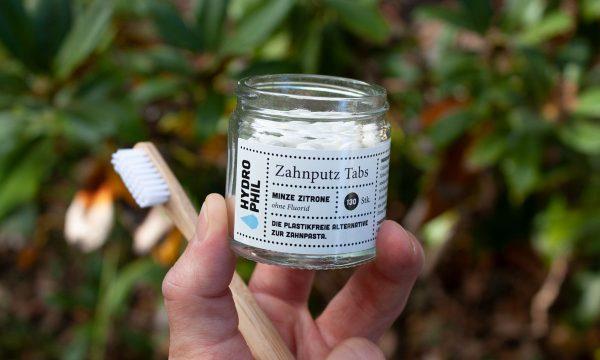 Hydrophil Zahnputz Tabs in der Hand mit Zahnbürste