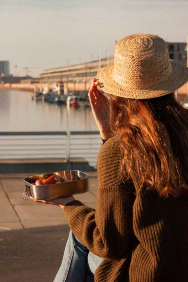 Mädchen sitzt am Hafen und isst Äpfel aus Ihrer Bentobox