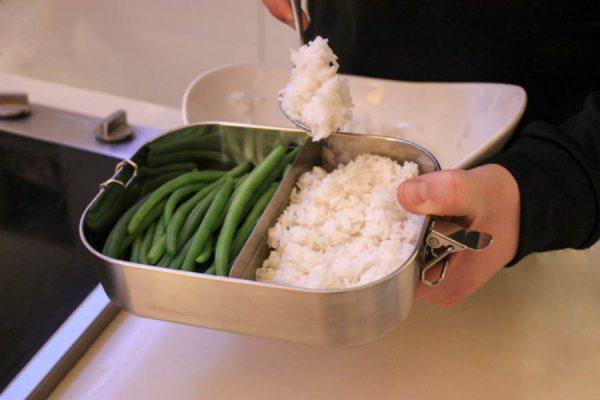 Die Bentobox mit einer Trennwand wird mit Reis und Bohnen befüllt