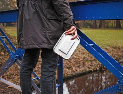Mann steht auf einer Brücke und hält die auslaufsichere Lunchbox aus Edelstahl in der Hand