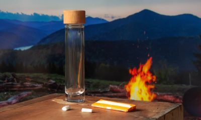 Reiseaschenbecher am Zeltplatz auf dem Tisch neben einem Lagerfeuer